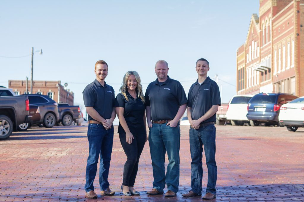 Grain Belt insurance team members, Ben, Taylor, Corey and Nolan, standing on brick street