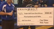 half court shot winner standing with an oversize five hundred dollar check