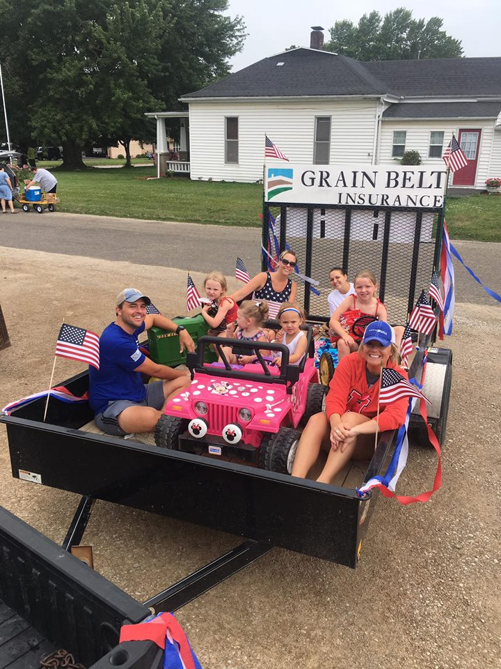 trailer decorated with American flags and Grain Belt insurance sign for parade with children and adults riding on it