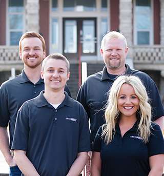 Grain Belt insurance team members, Ben and Corey in backrow, Taylor and Nolan in front row, standing in front of Troy courthouse